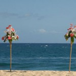 Twin tiki torches with flowers on beach
